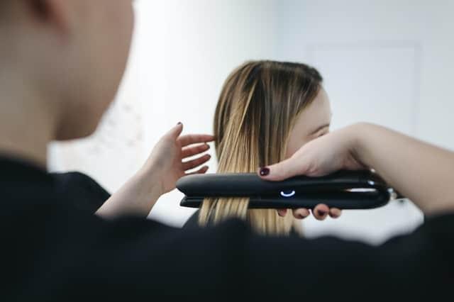 woman styling hair - hair salon punch cards loyalty program